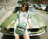 model in a dress is leaning against green car and wears a Green Patterned embroidered ABURY Leather Berber Shoulder Bag