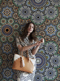 Model holding Rabbia Camel Leather Tote Bag against a Moroccan patterned wall