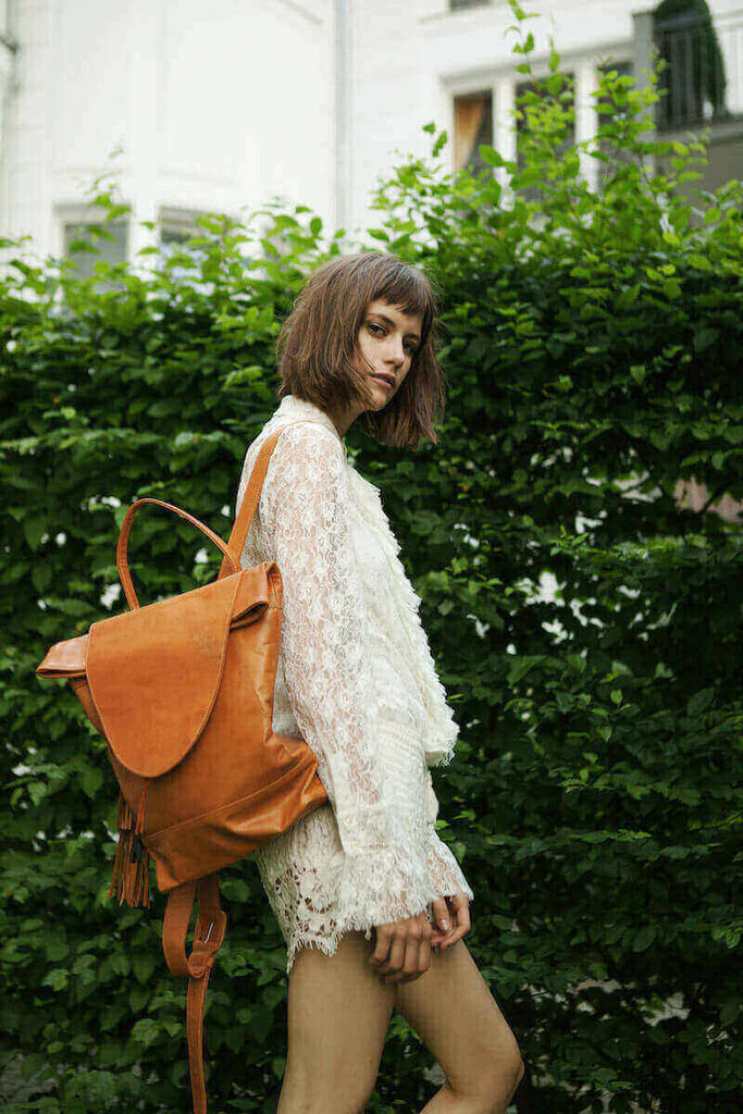 woman in front of hedge wearing saffron leather backpack