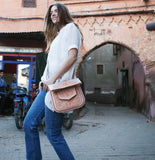 model in moroccan street wearing beige and peach embroidered ABURY Leather Berber Shoulder Bag
