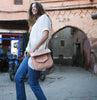 model in moroccan street wears beige and peach embroidered ABURY Leather Berber Shoulder Bag