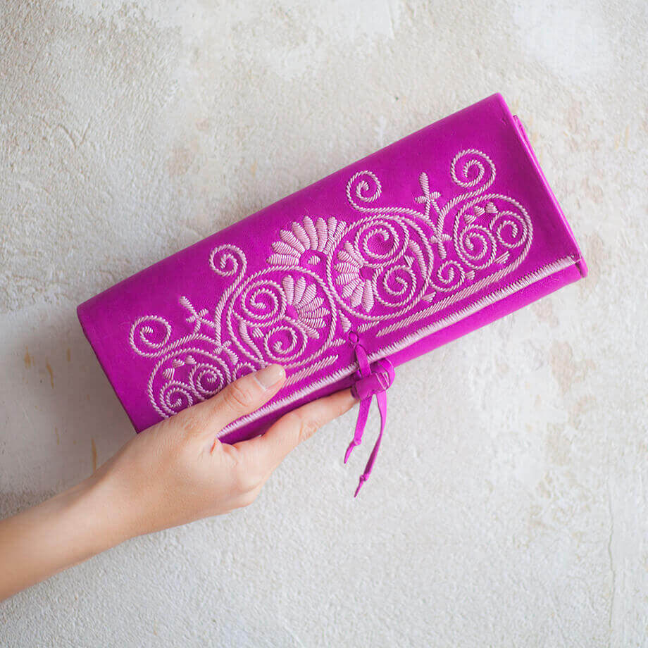 hand holding handmade pink and rose abury leather clutch bag