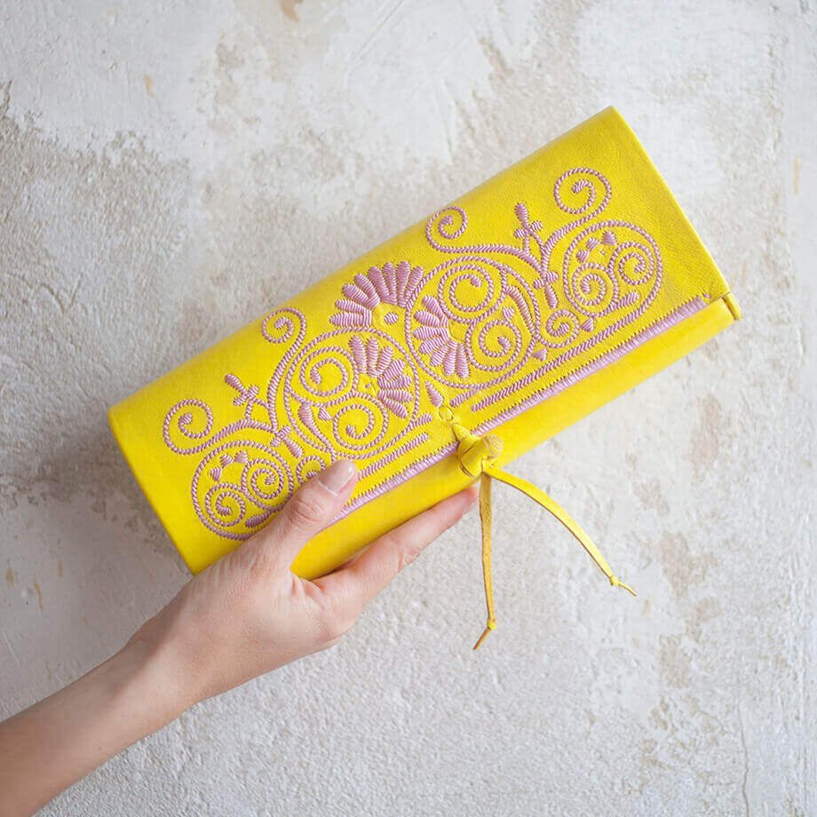 hand holding Yellow and Rosé abury Leather Clutch Bag sustainably fashionable