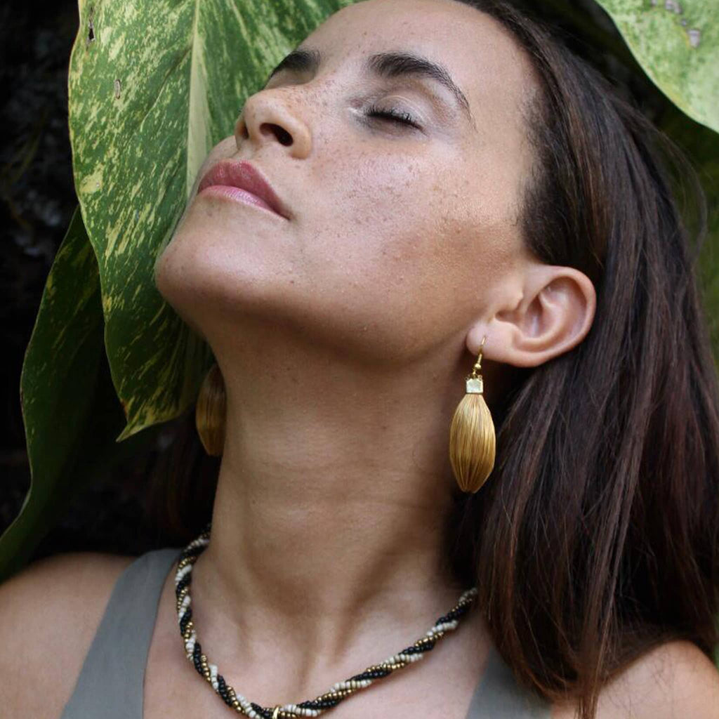 Model using paje golden grass earrings by she is from the jungle
