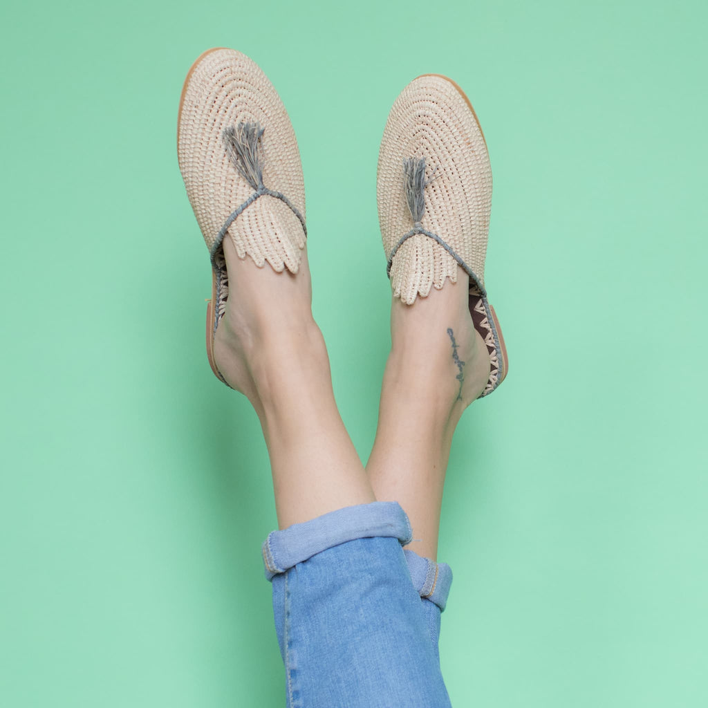 feet model in front of a green background wearing jeans and abury beige, grey raffia summer slippers with tassel