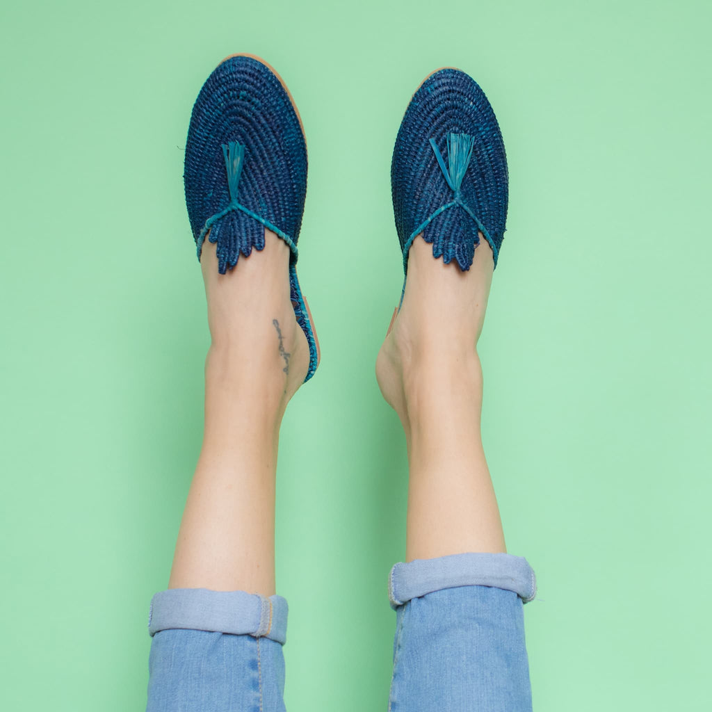 feet model in front of a green background wearing jeans and abury blue raffia summer slippers with tassel