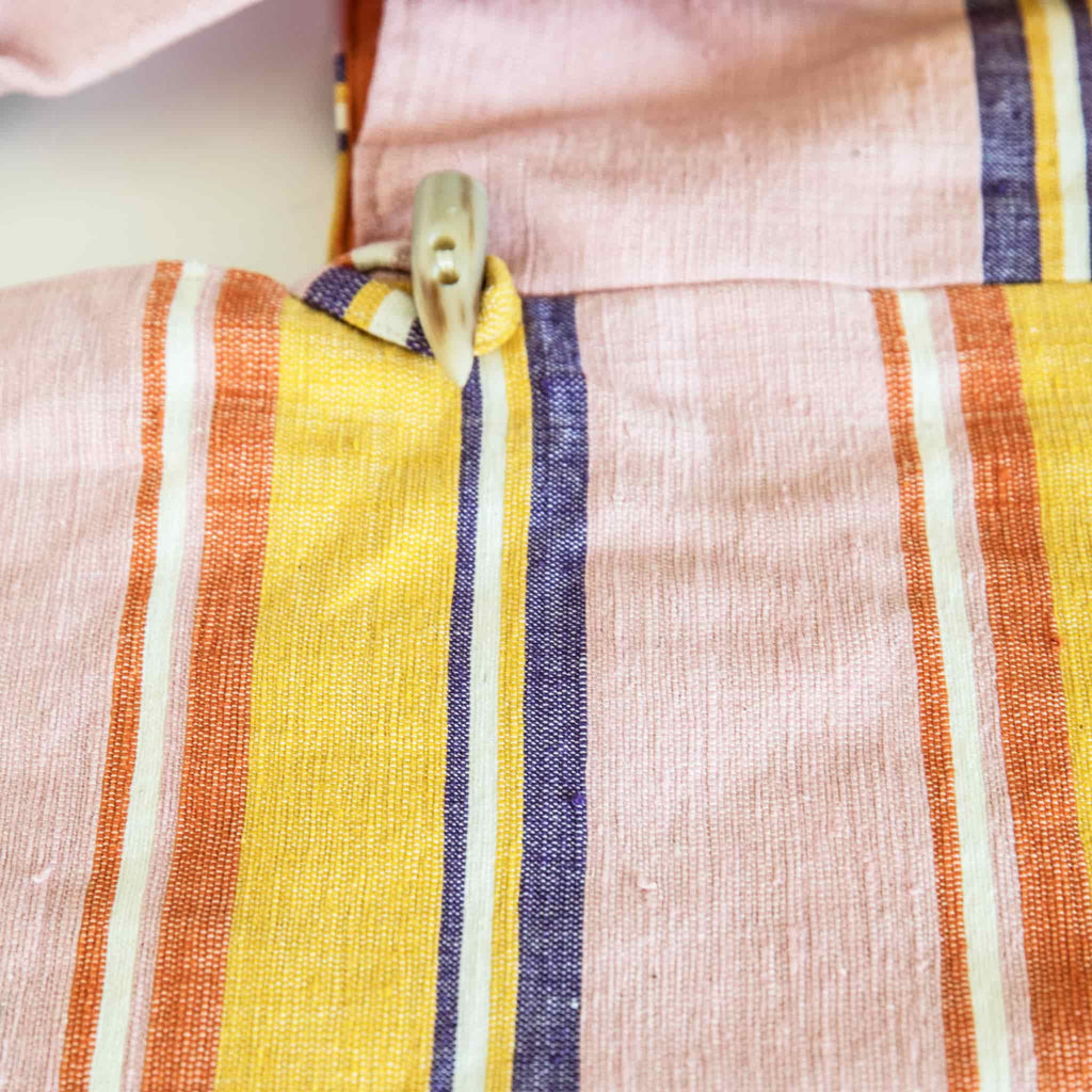 close up of the ABURY cotton hobo bag in pink and yellow with cow horn toggle button