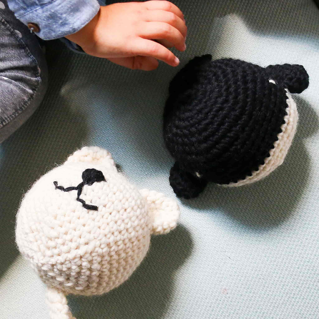 Baby hand reaching out for Whale & Cat Amigurumi - Black and White - Crochet kit- We Are Knitters