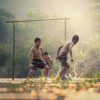 children playing football in nature