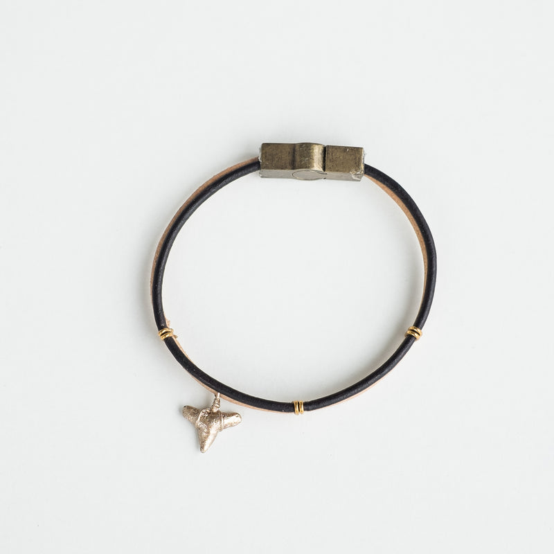 gold shark tooth bracelet on black and tan leather
