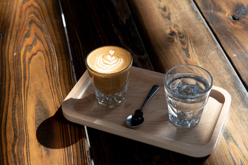 Gibraltar Espresso Drink sitting on a wooden board next to a glass of carbonated water