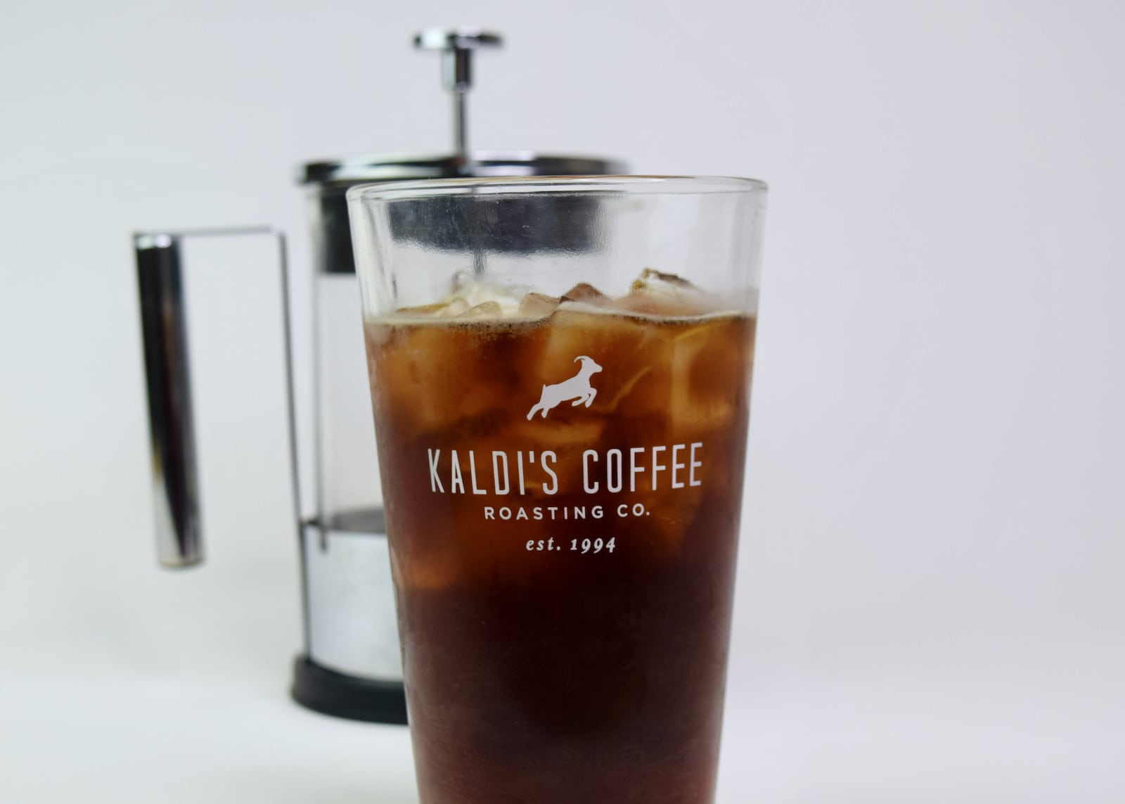 Glass of iced cold brew coffee next to a Yama 6 Cup French Press