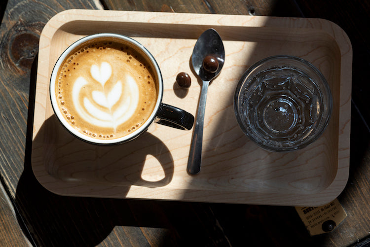 A finished espresso coffee drink with milk on a wooden board with seltzer water.
