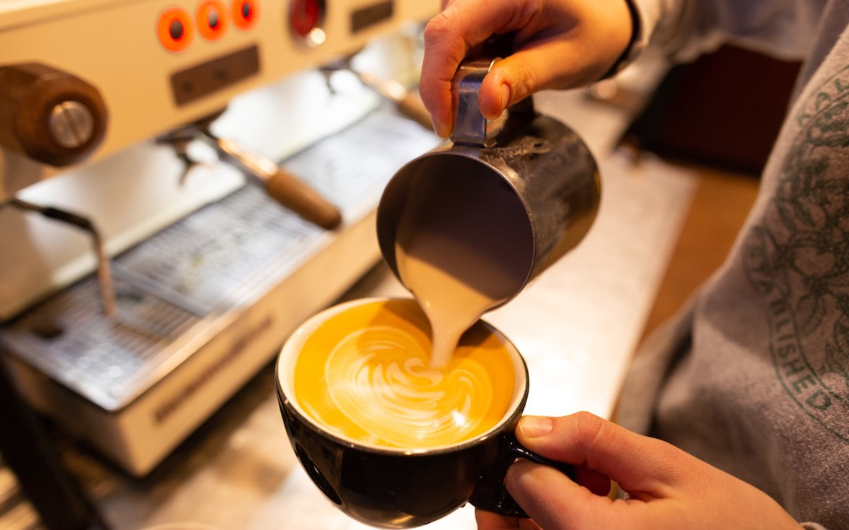 Kiersten pouring latte art in front of an espresso machine at one of our coffee shops