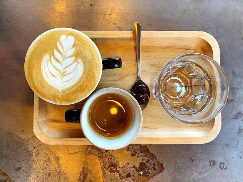 Cappuccino and a shot of espresso on a wooden board