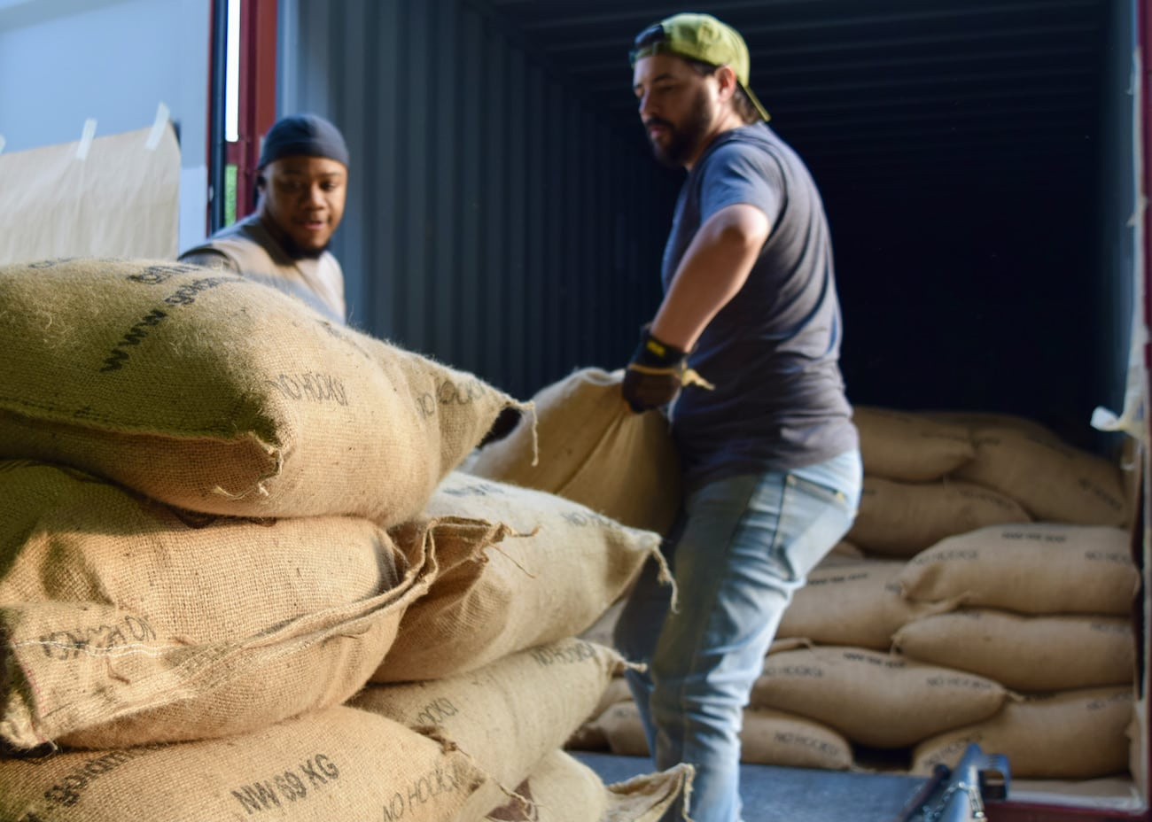 Unloading green coffee bags from a truck