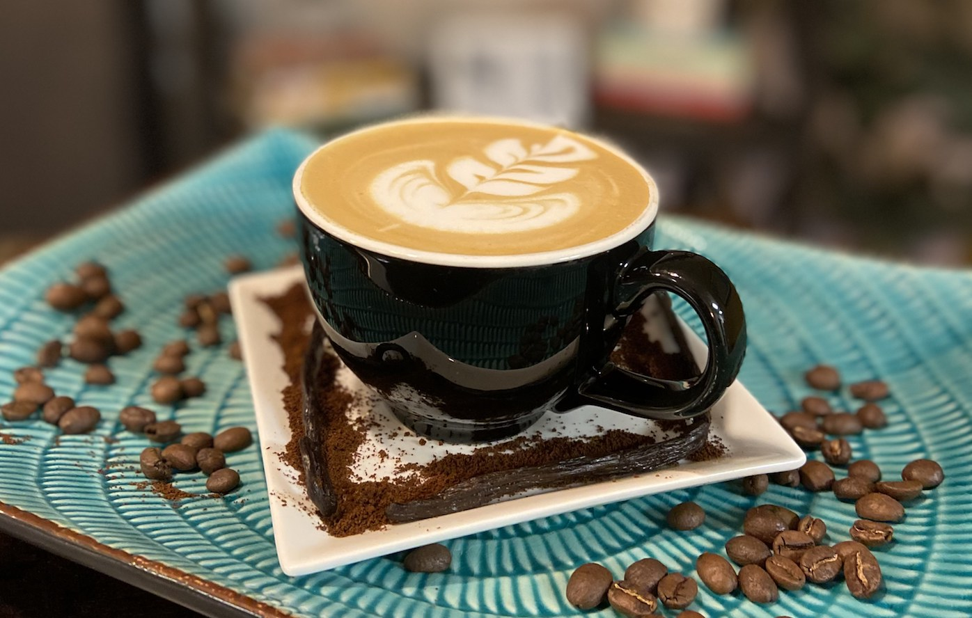 A Vanilla Latte on a blue plate with vanilla beans