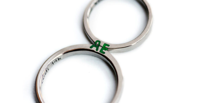 silver ring set with green initials