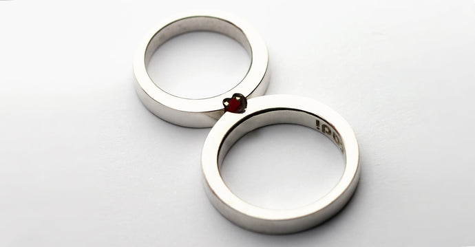 Gold couple promise rings set with red and blue gemstones and a secret heart shape
