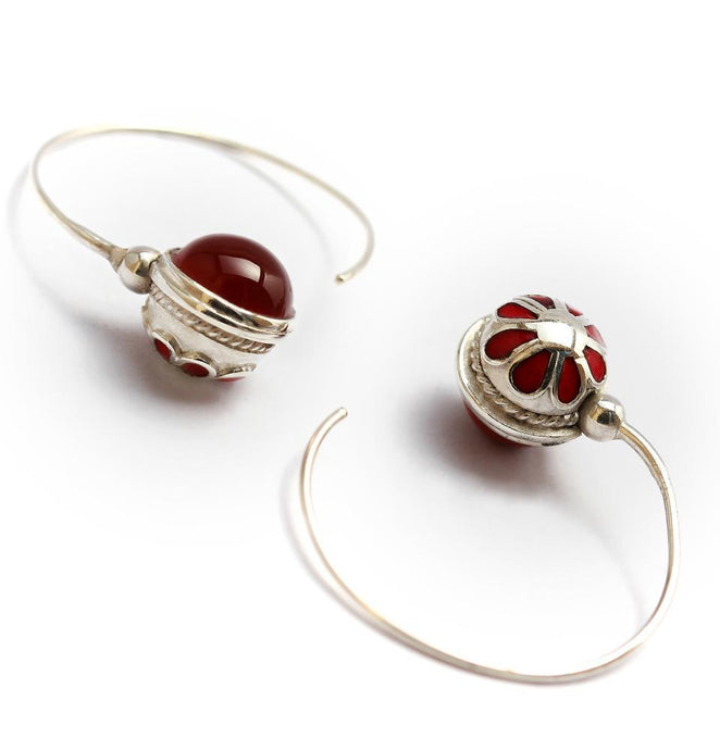 red gemstone in silver or gold earrings