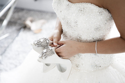 Bride holding embellished wedding shoes