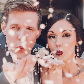 Wedding Couple Blowing Confetti