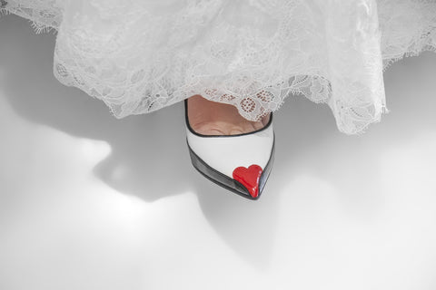 White wedding shoes with red heart at toe