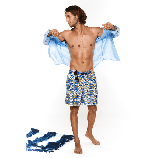 Male wearing light blue top next to beach towel wearing Fontainebleau swim shorts