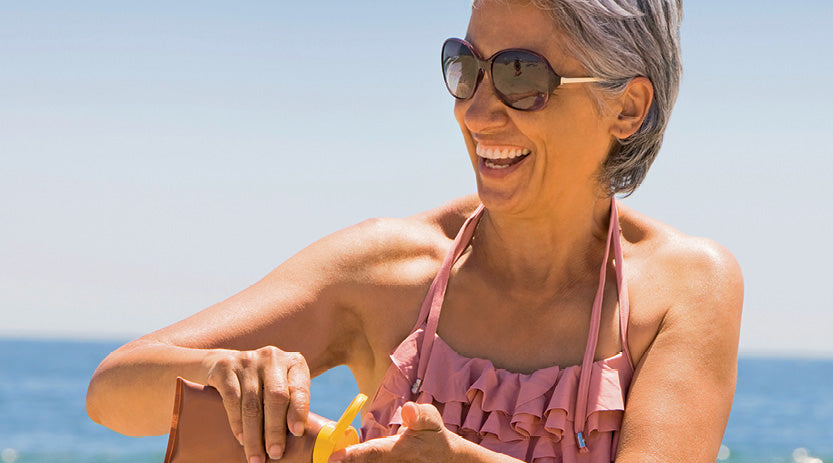 Older lady at the beach wearing sunglasses