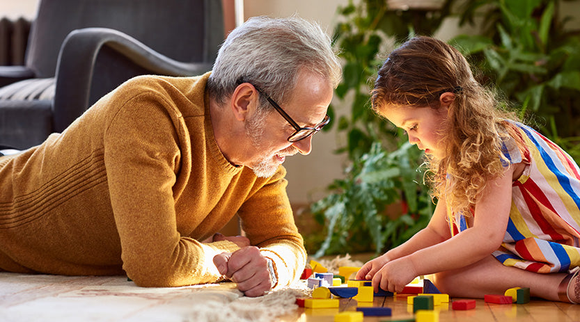 Granddad and granddaughter playing with blocks