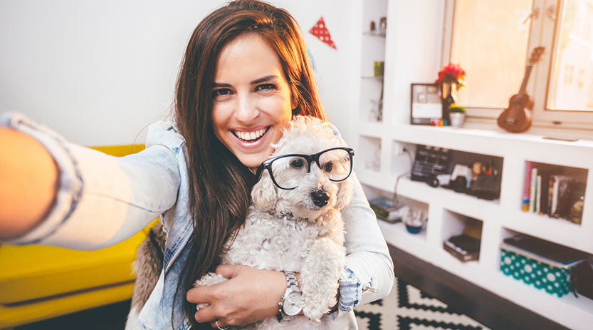 Lady holding a dog with glasses on