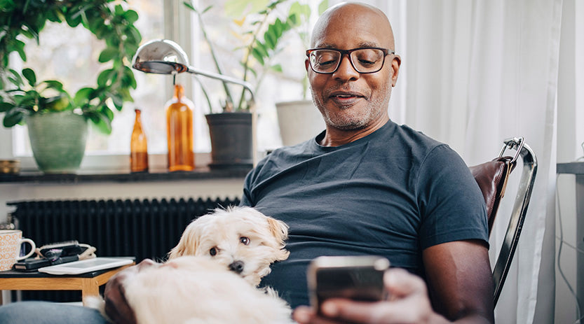 Mature man patting his dog and looking at his phone