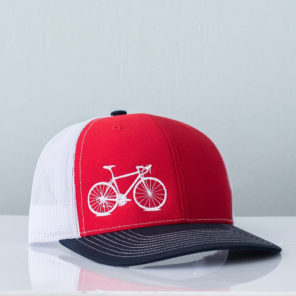 Red white and blue mesh back trucker hat embroidered with a cream bicycle