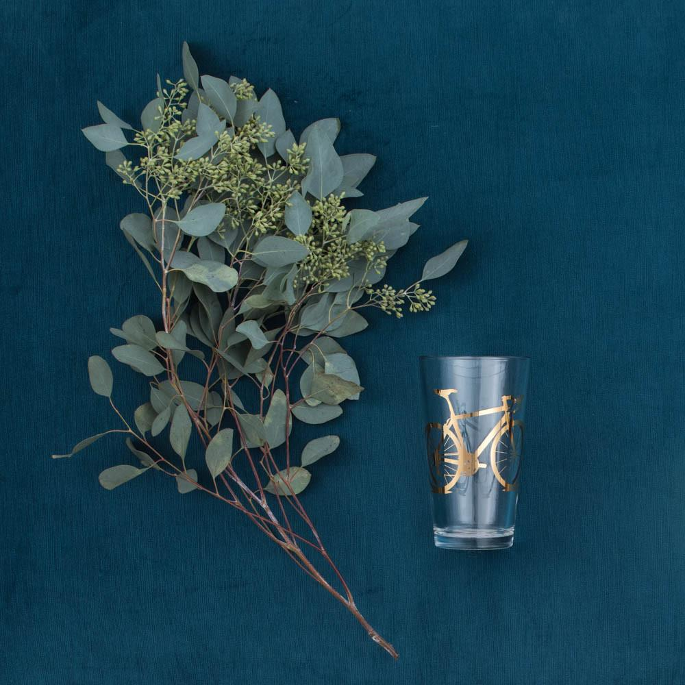 A eucalyptus bouquet and 20K gold bicycle pint glass on blue velvet.