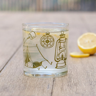 Camping equipment glassware tumbler screen printed with tent, compass, lantern on picnic table with cut lemons