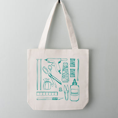 Crafting tools essentials including a hot glue gun, scissors, pin cushion, knitting and crochet needles screen printed on a tote