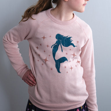 mermaid and sparkle screen print on rose cozy sweatshirt girl model with hand on hip