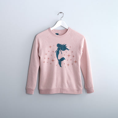 dark teal mermaid and rose sparkle screen printed soft cozy sweatshirt light pint hanging on white hanger in from of gray wall
