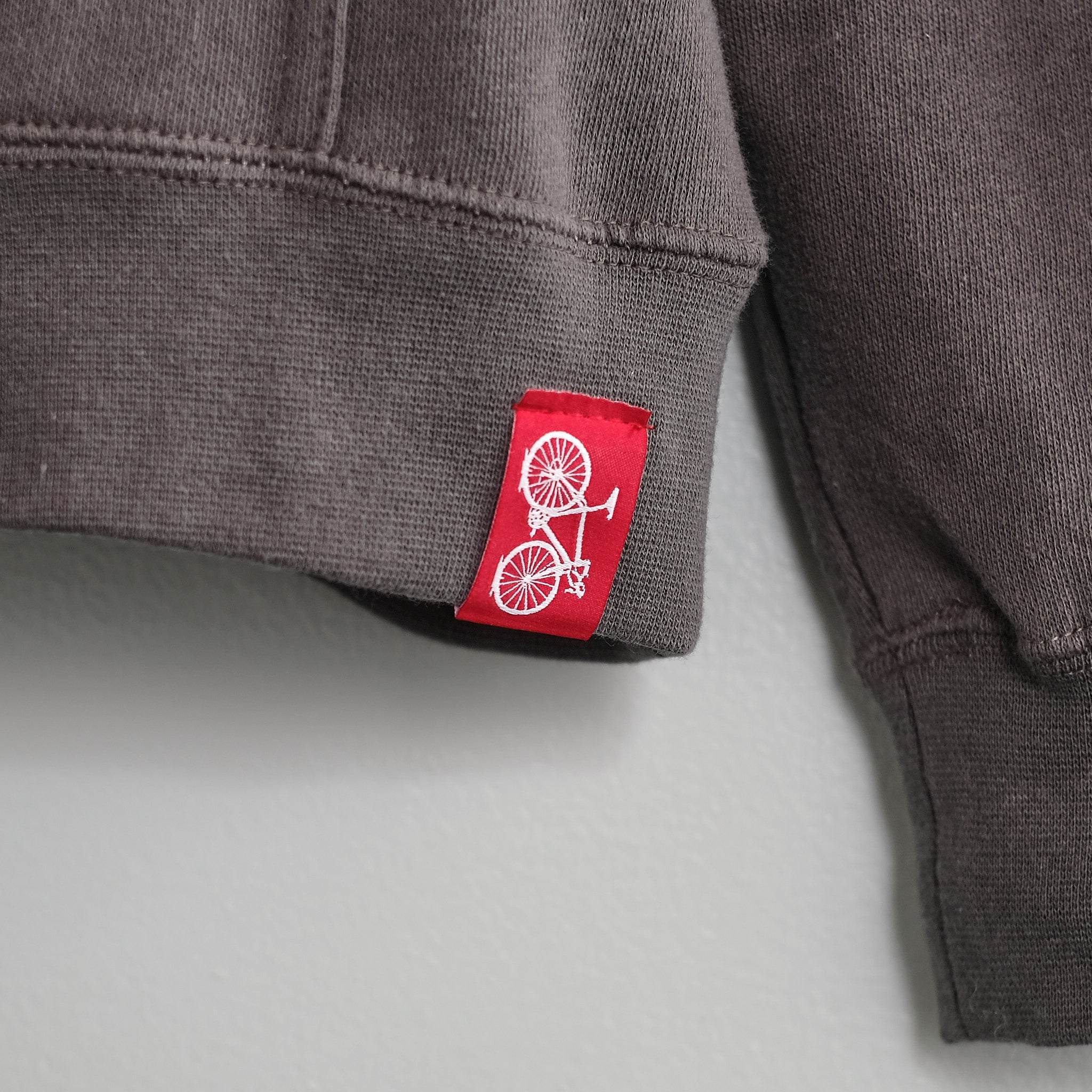 sewn bicycle tag detail red tag charcoal gray sweatshirt bike