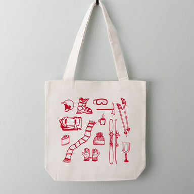 Red ski trip essentials featuring skis, ski boots, winter goggles, helmet, ski poles and gloves screen printed on a cotton canvas tote.