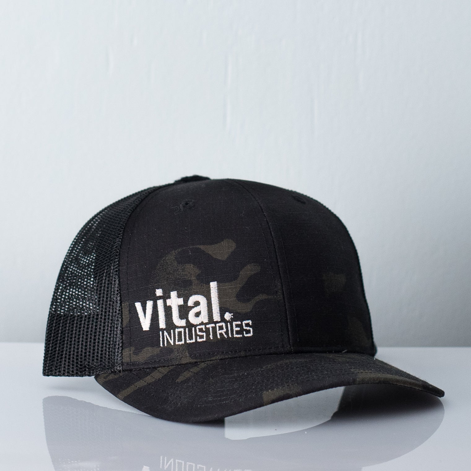 Dark camouflage mesh back trucker cap embroidered with Vital Industries logo in matte cream