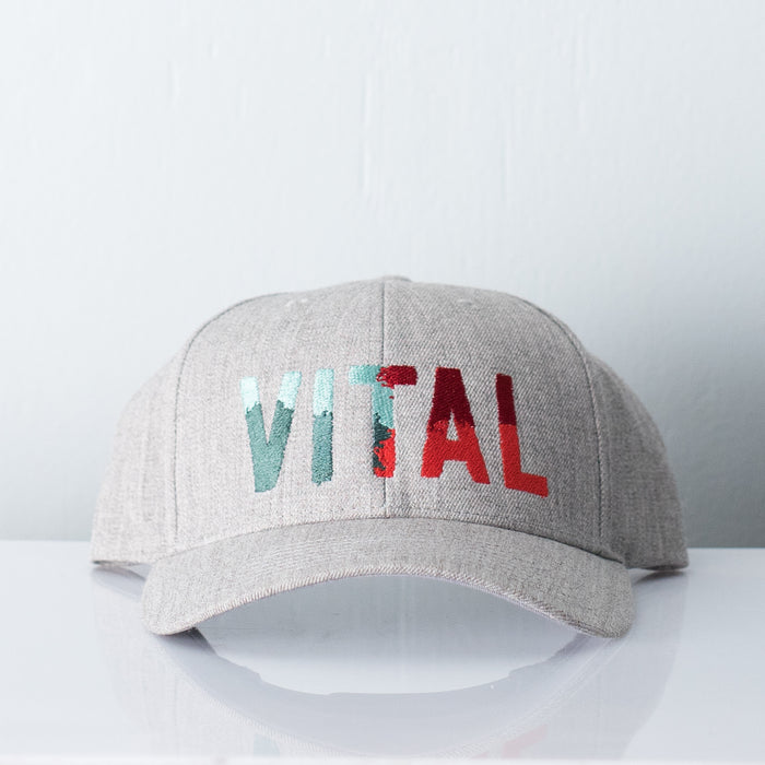 Grey melange hat embroidered with Vital Camo - a colorful logo displaying light blue, teal, electric red and maroon