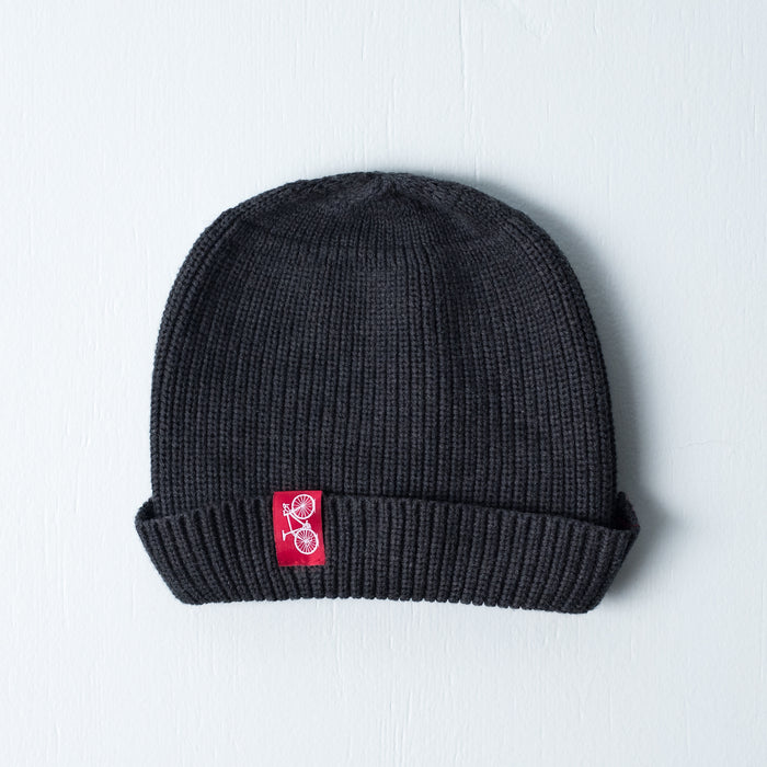Grey dock beanie with red sewn on bicycle tag