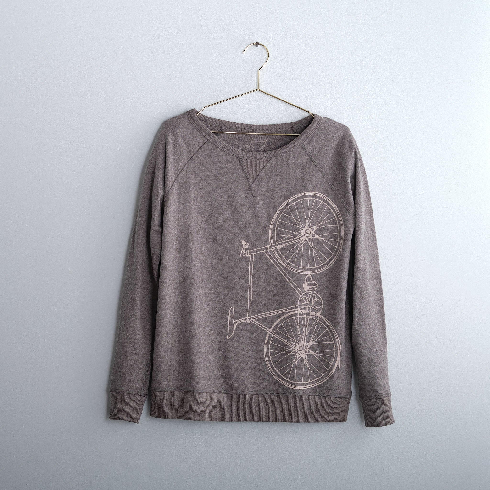 gray heather bicycle French Terry sweatshirt light pink bike screen print on gold hanger in front of gray wall