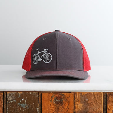 road bike embroidered trucker cap charcoal  red bicycle hat on white table