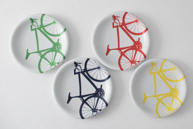 Flatlay of bicycle plate set including green, navy, red and yellow