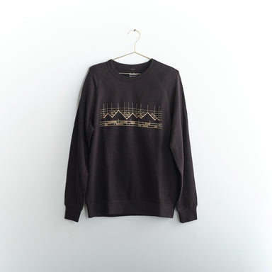 Black unisex French Terry sweatshirt with gold geometric mountain screen print hanging on gold hanger in front of white wall