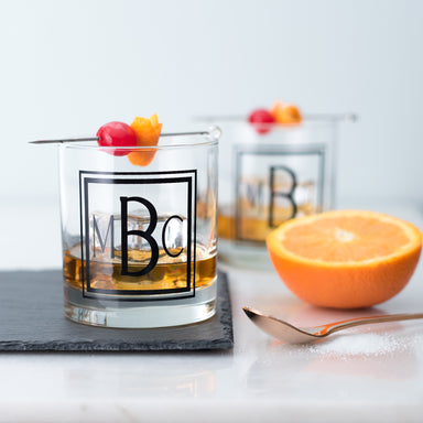 Custom monogram old fashioned cocktail glassware on a slate coaster set featuring an orange and cherry garnish