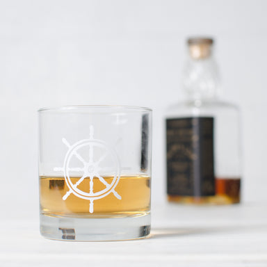 While ship wheel screen printed on a rocks glass and filled with liquor
