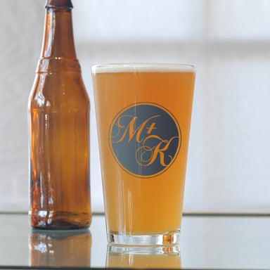Custom circle monogram on a 16 oz. pint glass filled with beer